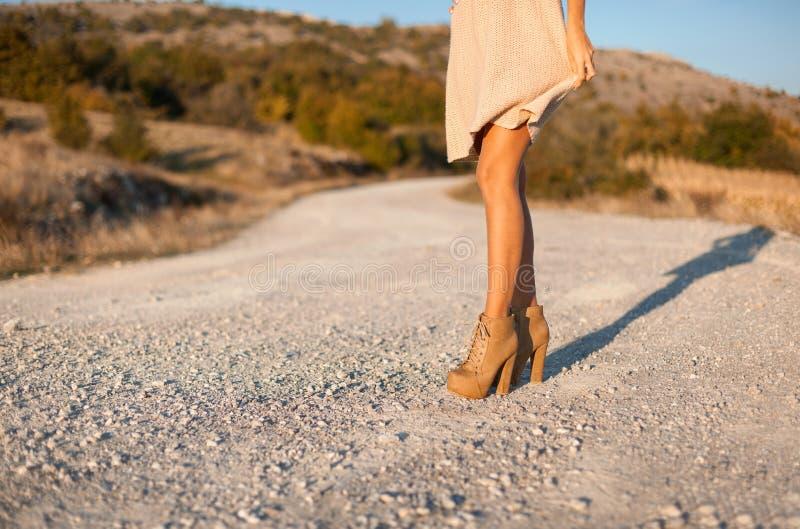 Kvinnaben på skor för höga häl arkivbild