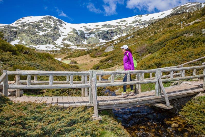 Kvinnabergsbestigare som korsar en bro över en ström som ser berget arkivbilder