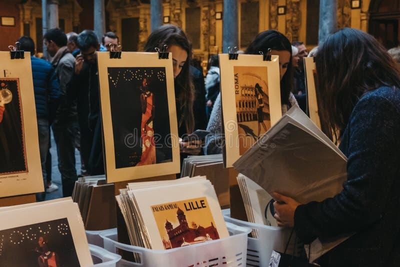 Kvinnabläddrandeaffischer på den begagnade boken marknadsför i borggården av den gamla börsen för den Vieille börsen i Lille, Fra royaltyfria foton