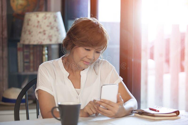 Kvinnablick- och läsningmeddelande i smart telefonskärm arkivbild