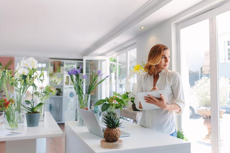 Kvinnablomsterhandlare som arbetar i blomsterhandel royaltyfria bilder
