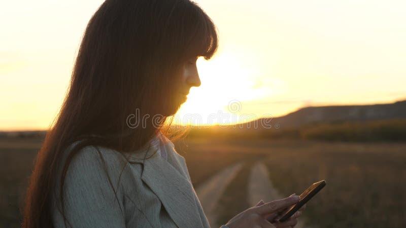 Kvinnabonde som arbetar med en minnestavla i fält i solsken flickans hand skrivar ut ett mobilt meddelande på smartphoneskärmen royaltyfri bild