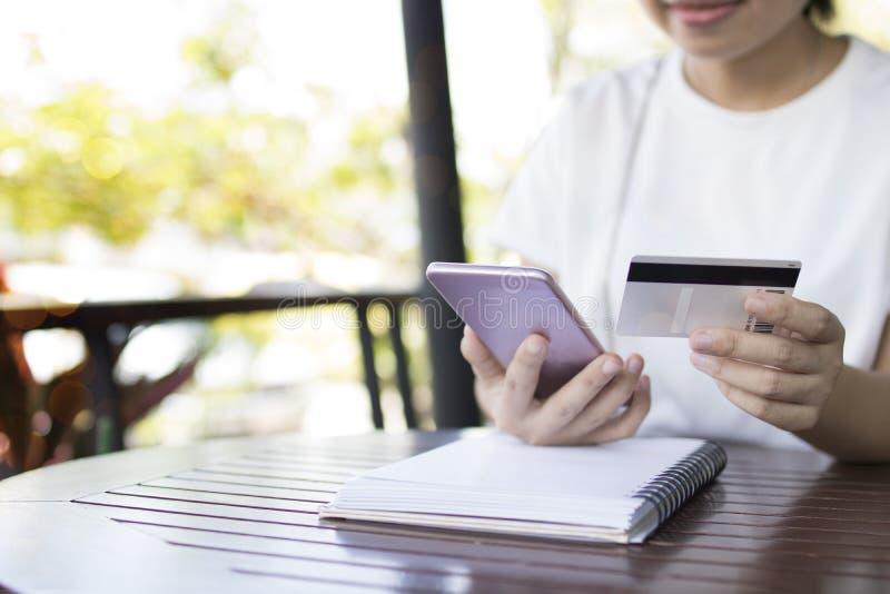 Kvinnabrukstelefon för mobila bankrörelsen med kreditkorten till online-sh royaltyfri bild