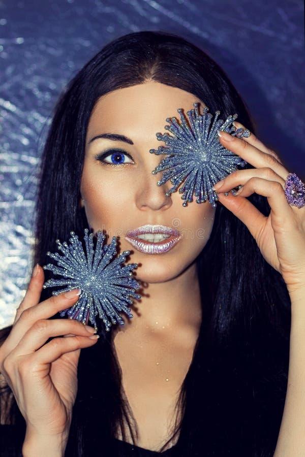 Kvinnabrunett med julpyntsilversnöflingor fotografering för bildbyråer