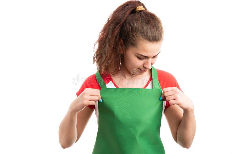 Kvinnabutiksinnehavare eller detaljhandelarbetare som justerar hennes förkläde arkivfoto