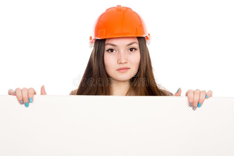 Kvinnabyggmästare i en hjälm med ett tomt baner royaltyfri foto