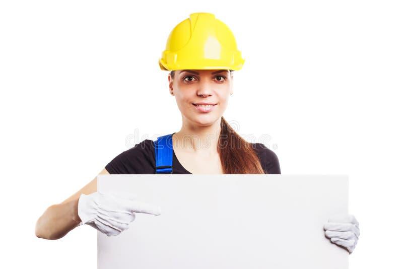Kvinnabyggmästare i konstruktionshjälm med ett plakat royaltyfria foton