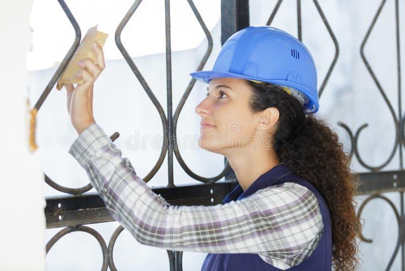 Kvinnabyggmästare som arbetar på att fäkta för metall arkivbild