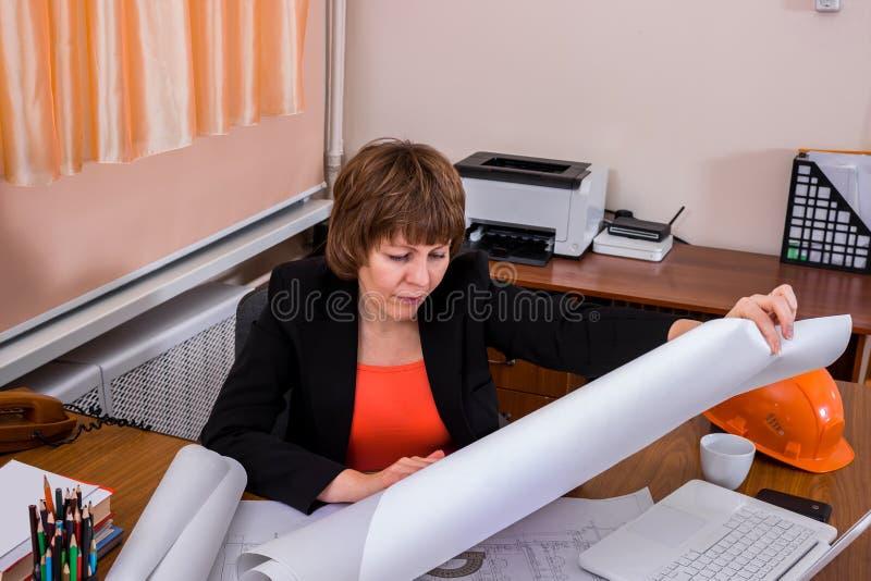 Kvinnabyggmästaretekniker som ser ritningpapper fotografering för bildbyråer