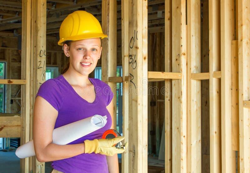 Kvinnabyggnadsarbetare som rymmer arkitektoniska teckningar royaltyfri foto