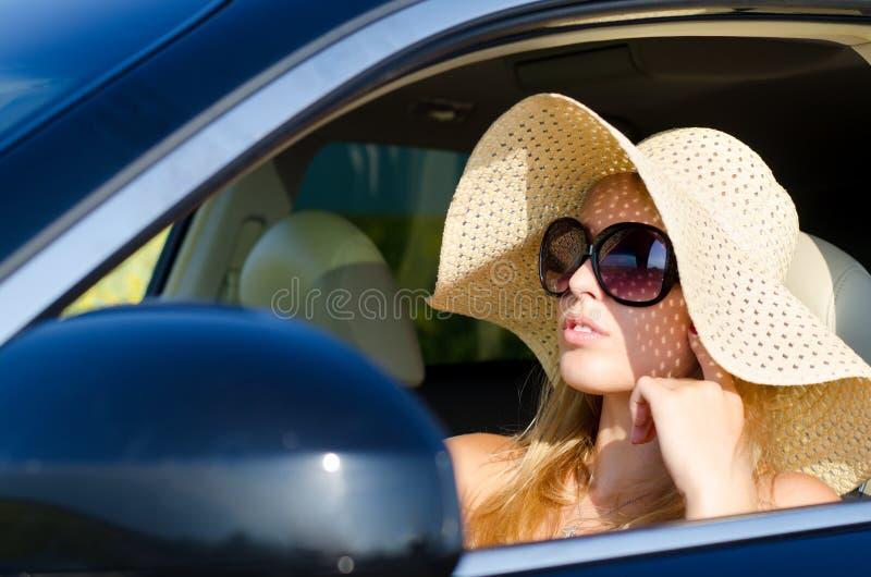 Kvinnachaufför i sunhat och solglasögon arkivfoto