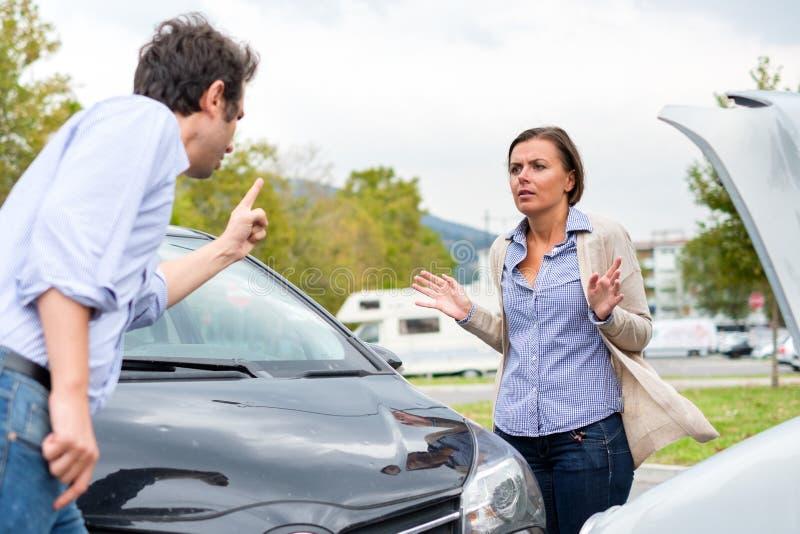 Kvinnachaufför och man som argumenterar om skadan av bilen efter a fotografering för bildbyråer