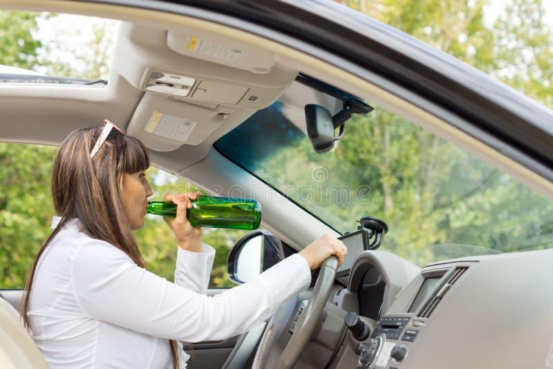 Kvinnachaufför som dricker och kör hennes bil fotografering för bildbyråer