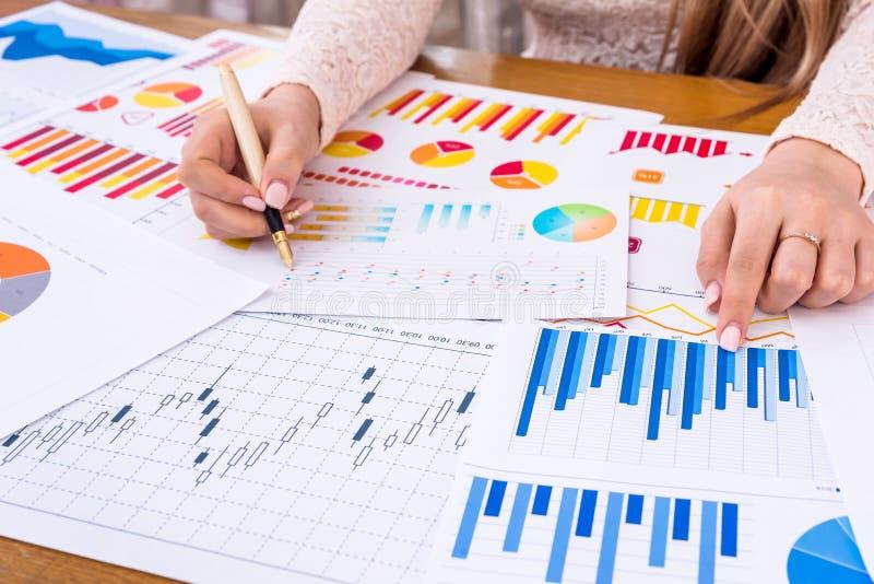 Kvinnachef som arbetar med affärsgrafer och diagram arkivbilder