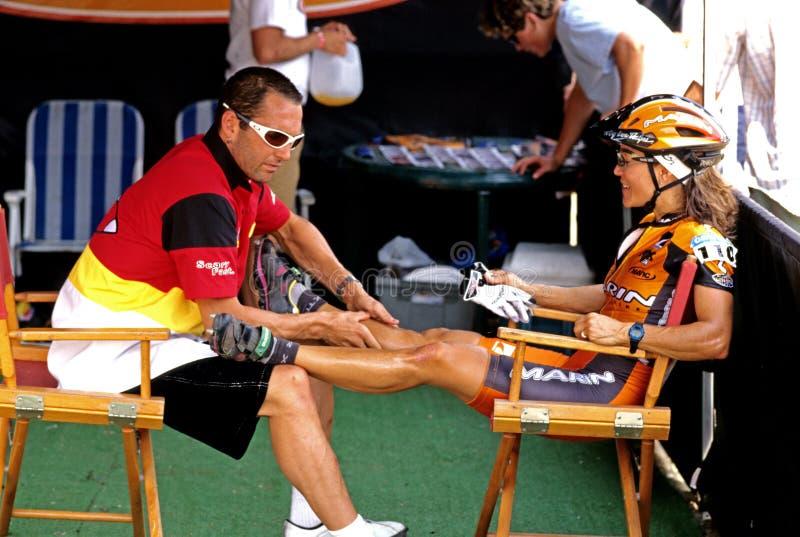 kvinnacyklist som får benmassage royaltyfria foton