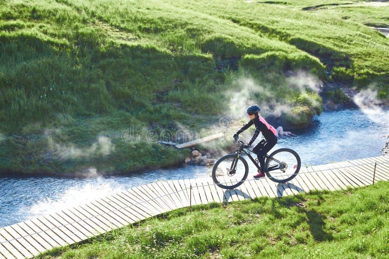 Kvinnacyklisten cyklar ner lutningen i dalen av floden av Hveragerdi Island arkivfoto