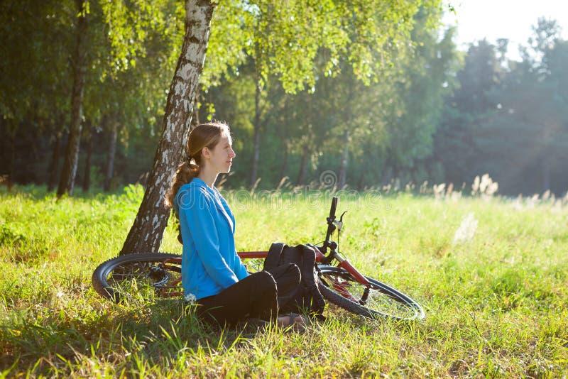 Kvinnacyklisten som tycker om avkoppling i soligt, parkerar arkivfoto