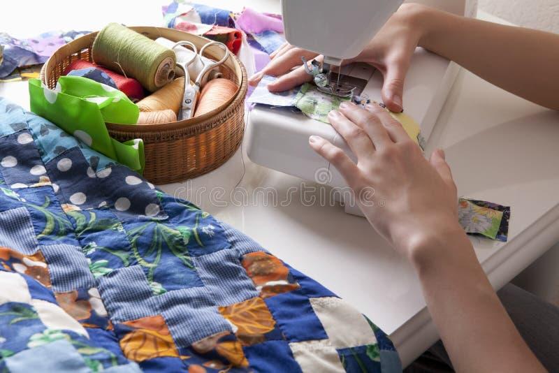 Kvinnadanandepatchwork på symaskinen arkivfoto