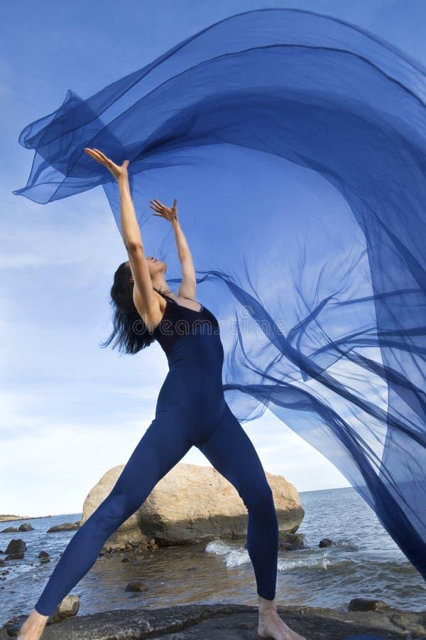Kvinnadans med blått tyg på stranden i Connecticut royaltyfri bild