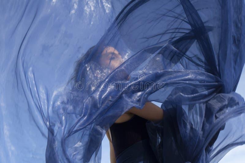 Kvinnadans med blått tyg på stranden i Connecticut fotografering för bildbyråer
