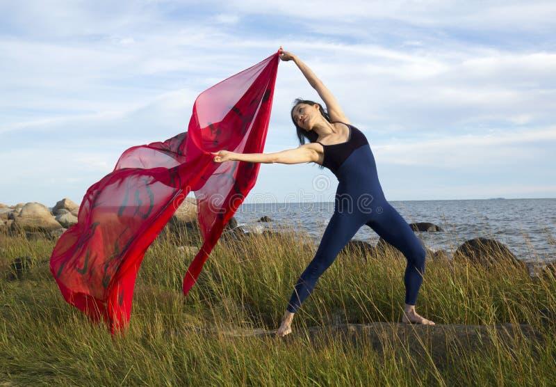 Kvinnadans med rött tyg på stranden i Connecticut royaltyfria foton