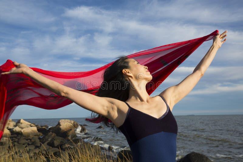 Kvinnadans med rött tyg på stranden i Connecticut arkivfoto