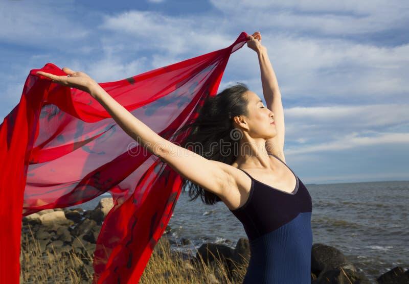 Kvinnadans med rött tyg på stranden i Connecticut arkivbild