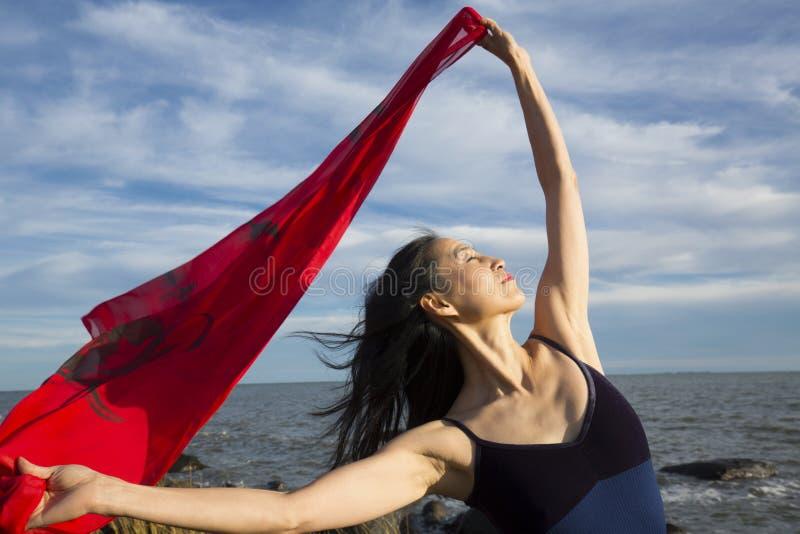 Kvinnadans med rött tyg på stranden i Connecticut arkivbilder