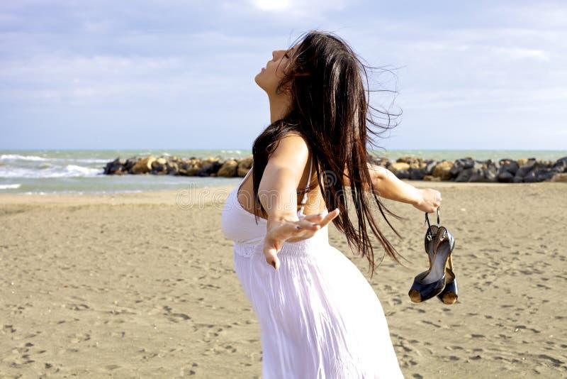 Kvinnadansen på stranden med ögon stängde sig och att blåsa för vind arkivbilder