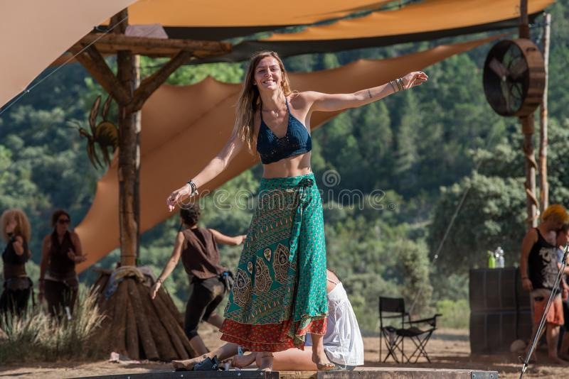Kvinnadanser på en plattform och blickar på kameran på den borttappade festivalen för teoripsytranscemusik som rymms i Riomalo de arkivfoto