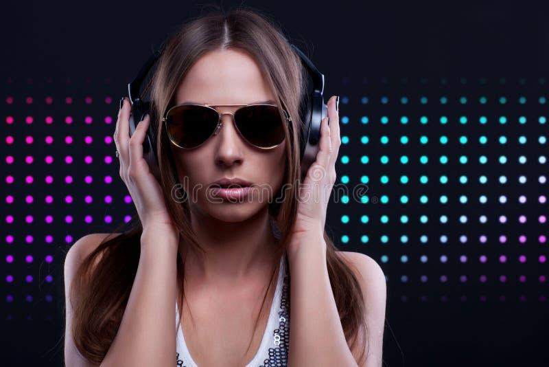 Kvinnadiscjockey som tycker om musiken i hörlurar royaltyfri foto