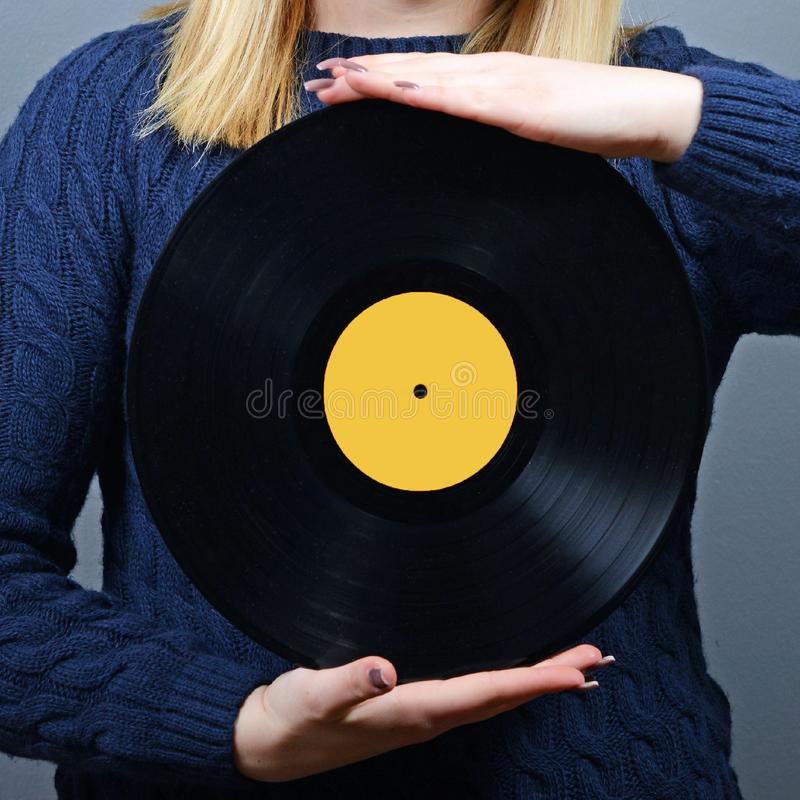 Kvinnadj-stående med vinylrekordet mot grå bakgrund arkivfoto