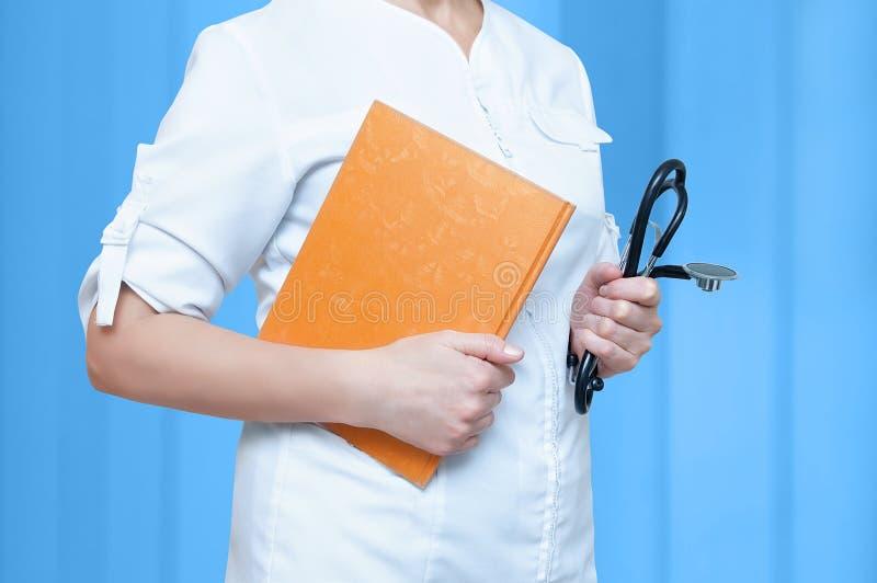 Kvinnadoktor i ett doktorskontor med en notepad och en stetoskop i händer på en blå bakgrund royaltyfri fotografi