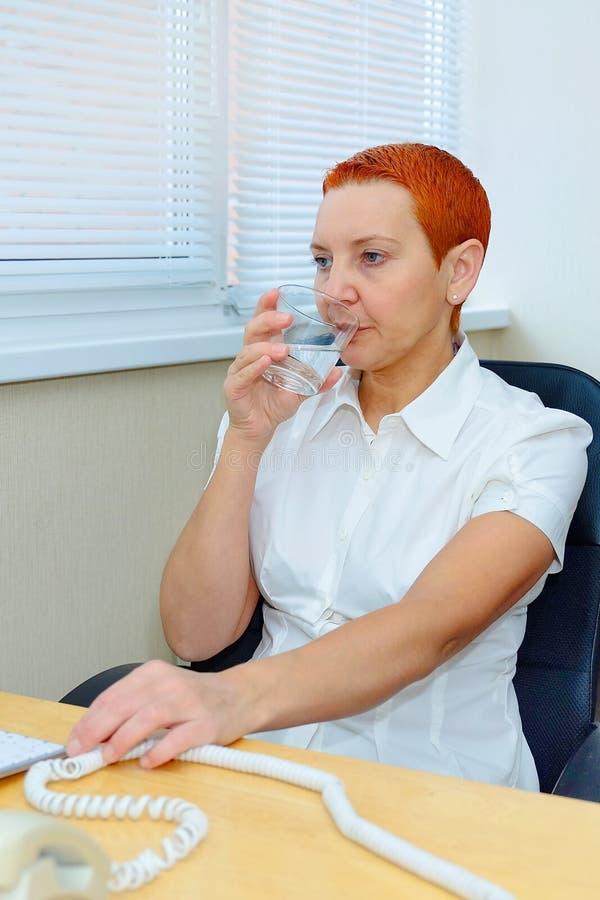 Kvinnadoktor i kliniken en minut vilar en SMUTT av vatten från exponeringsglaset arkivfoto