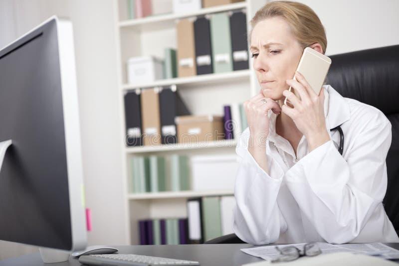 Kvinnadoktor Listening till någon över telefonen arkivfoton