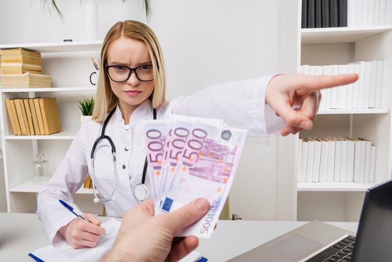 Kvinnadoktor med stetoskopet som v?grar mutor, eller mutor, valutor euro, patient som ger pengar f?r medicinsk service, begrepp a royaltyfri foto