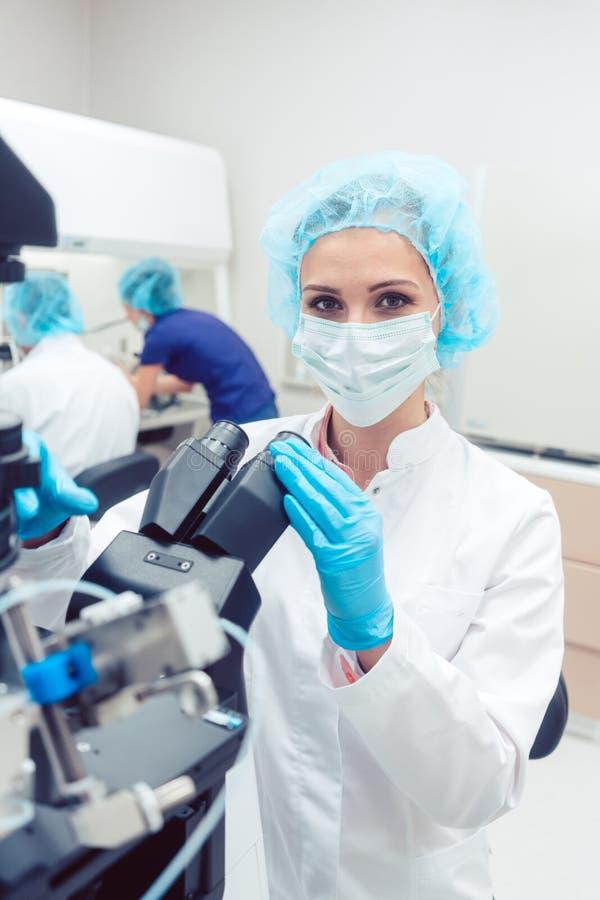 Kvinnadoktor som arbetar på manipulatoren som gödslar mänskliga ägg royaltyfri bild