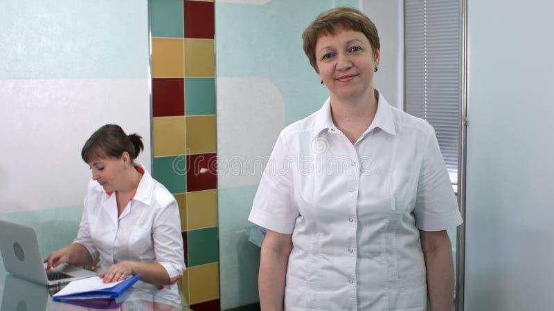 Kvinnadoktor som ler och ser till kameran, medan hennes kollega arbetar på bärbara datorn arkivbild