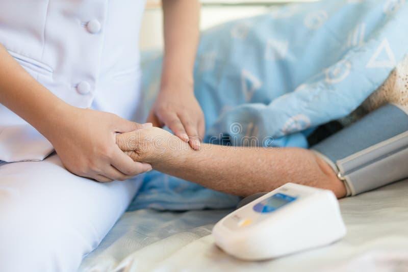 Kvinnadoktor som mätas i blod av den äldre patienten i hosna royaltyfri bild