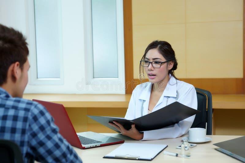 Kvinnadoktor som talar till hennes manliga patient på kontoret arkivbilder