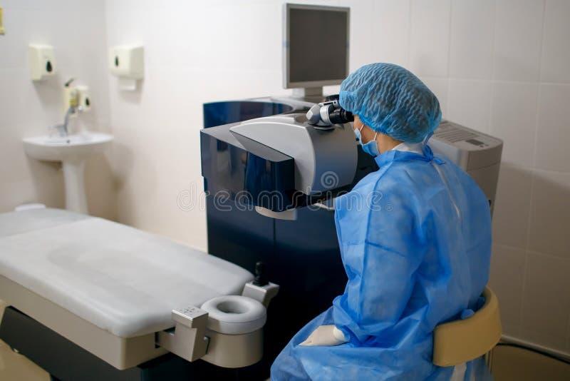 Kvinnadoktorn sitter på hans arbetsplats och ser till och med ett mikroskop, en forskare arbetar, en ögondoktor arkivbilder