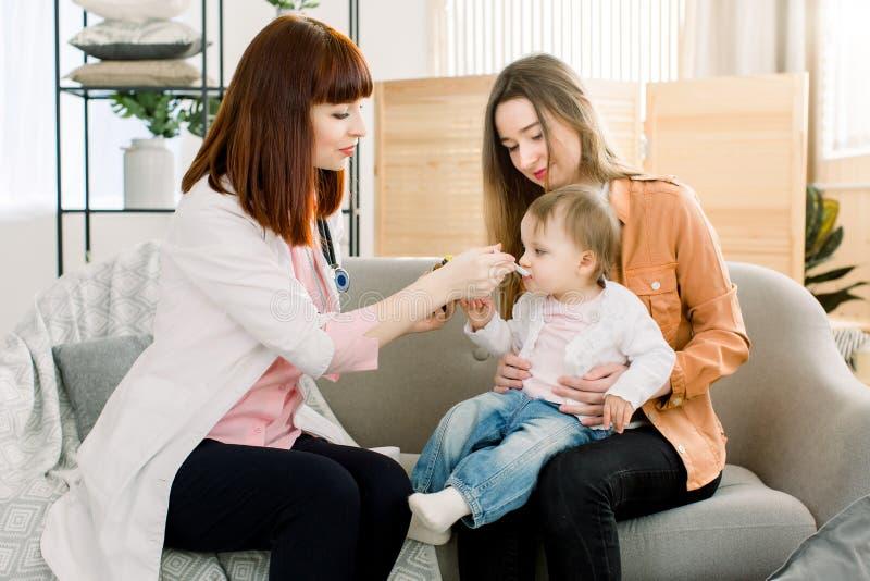 Kvinnadoktorn som ger skeddosen av medicinflytande som dricker sirap till barnet, behandla som ett barn flickan hennes patient Do arkivbilder