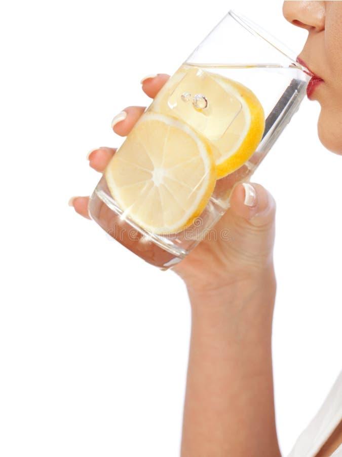 Kvinnadricksvatten med citronen royaltyfria bilder