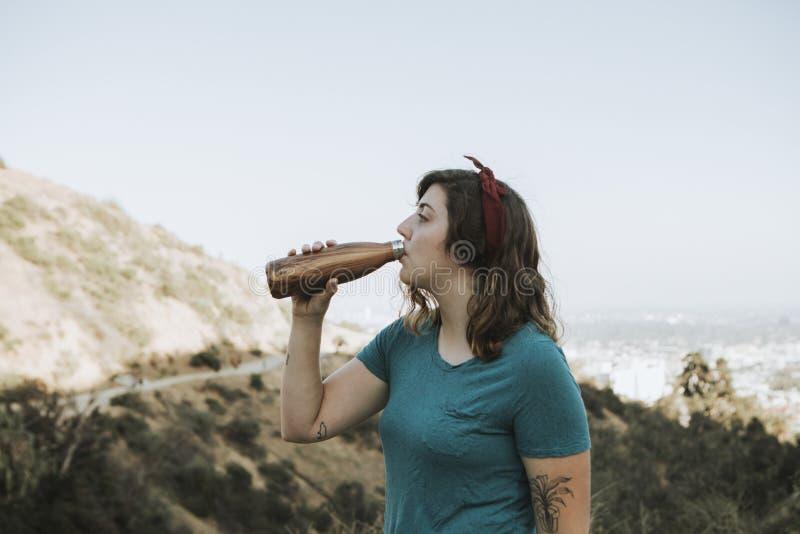 Kvinnadricksvatten, medan trekking arkivfoto