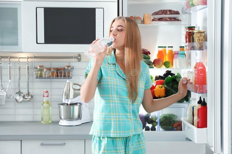Kvinnadricksvatten ut ur flaskan nära kylskåpet royaltyfri foto