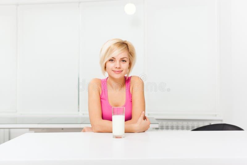 Kvinnadrinkexponeringsglas av mjölkar i hennes kök fotografering för bildbyråer