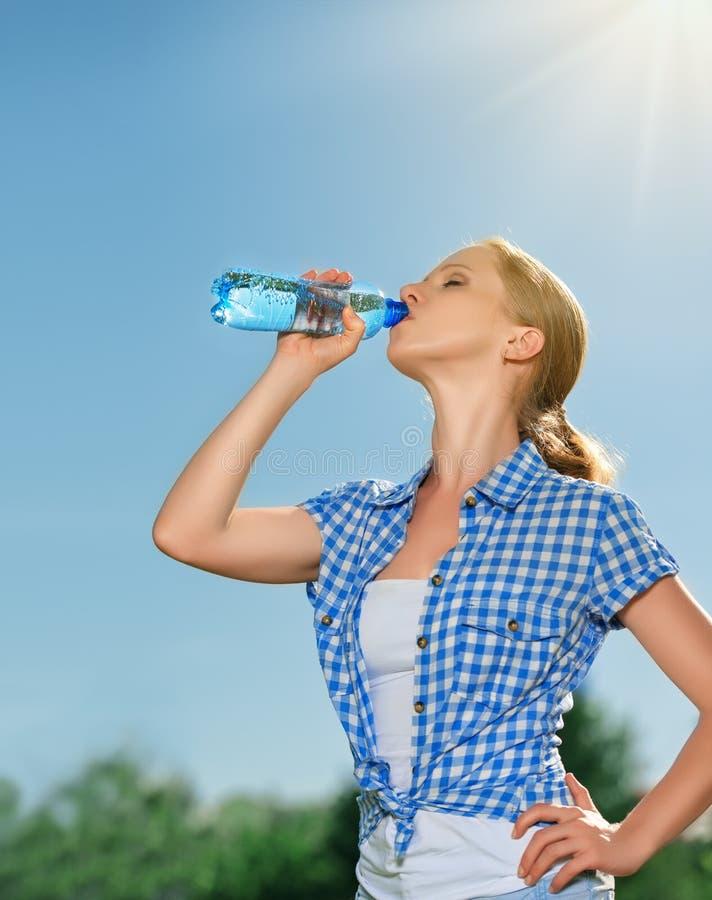 Kvinnadrinkvatten från en flaska i sommaren utomhus på set arkivfoton