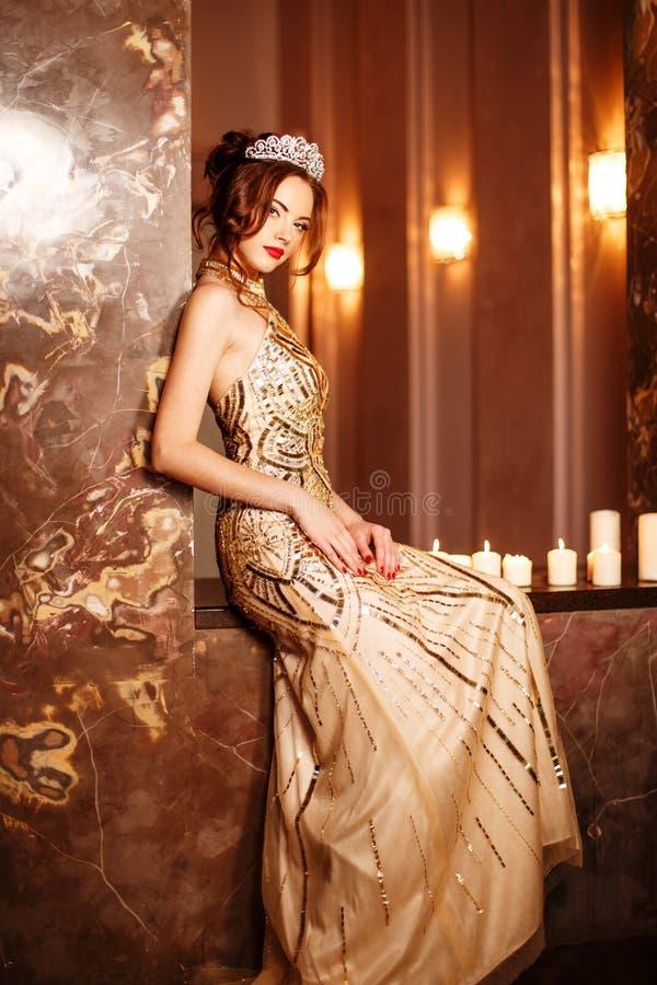 Kvinnadrottningprinsessan i kronan och luxklänningen, ljus festar backgr arkivfoto