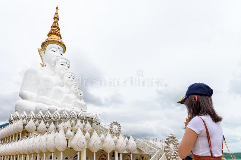 Kvinnadyrkan med Buddhastatyn fotografering för bildbyråer
