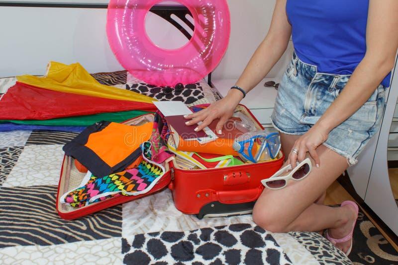 Kvinnaemballage som förbereder sig för sommarsemester Ung flickaemballageresväska på säng hemma royaltyfri fotografi